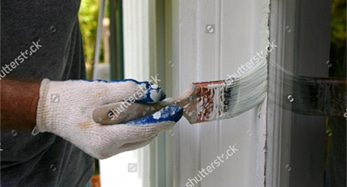 Person meticulously painting window trim